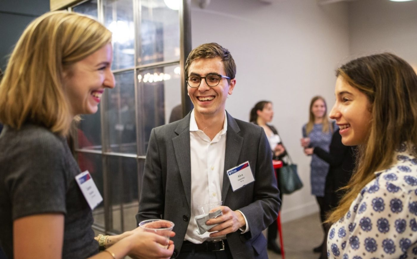 Young Alumni talking and laughing at NYC event